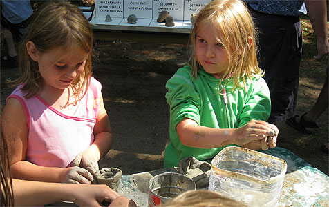 photo of two girls making clay pots