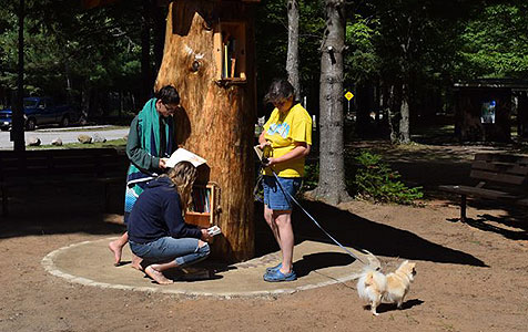 visitors reading at the book tree